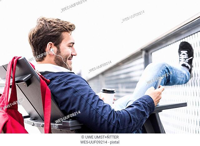 USA, New York, Businessan in Manhattan using smart phone and earphones