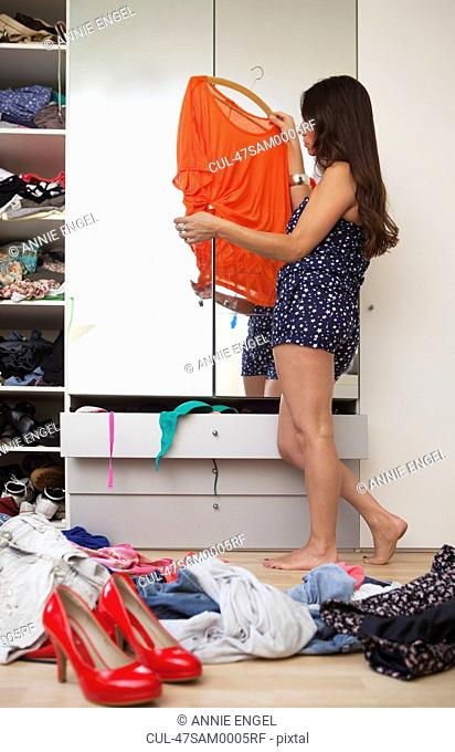 Woman trying on outfit in bedroom