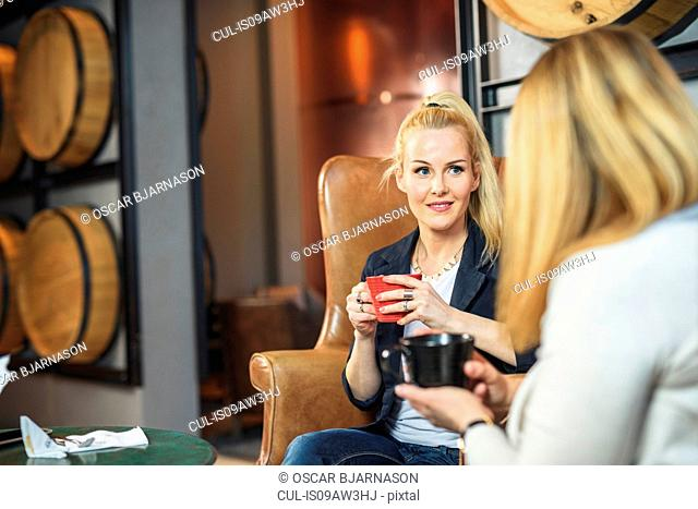 Mid adult woman sitting in leather armchair in public house holding coffee cup looking at friend smiling