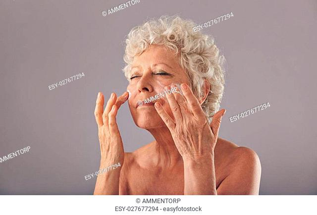 Portrait of beautiful old woman applying moisturizer on her face against grey background. Senior woman using cosmetics on her face