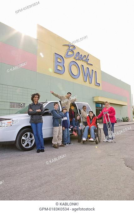 Portrait of multi-ethnic teenagers and woman with crutches standing next to mini van in bowling alley parking lot