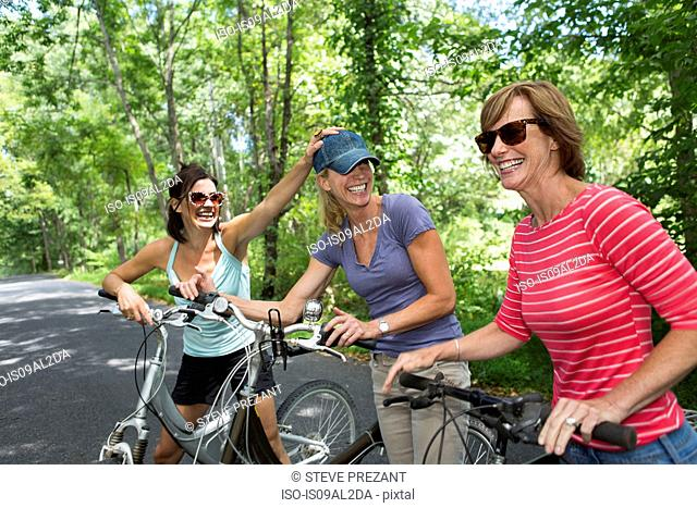 Three mature woman with bicycles along country road