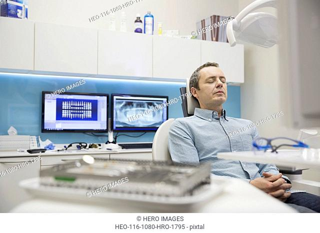 Patient sitting with eyes closed in dentists chair