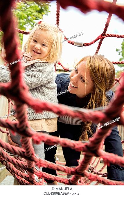 Mother and toddler daughter on playground climbing frame