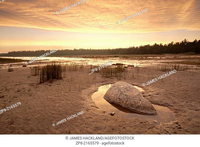 A rock sits in a small pool of water under a hazy sunset causing very warm and unusual light conditions at Singing Sands, Bruce Peninsula National Park, Ontario