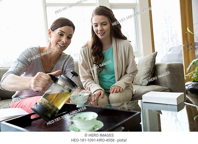 Mother and daughter pouring tea in living room
