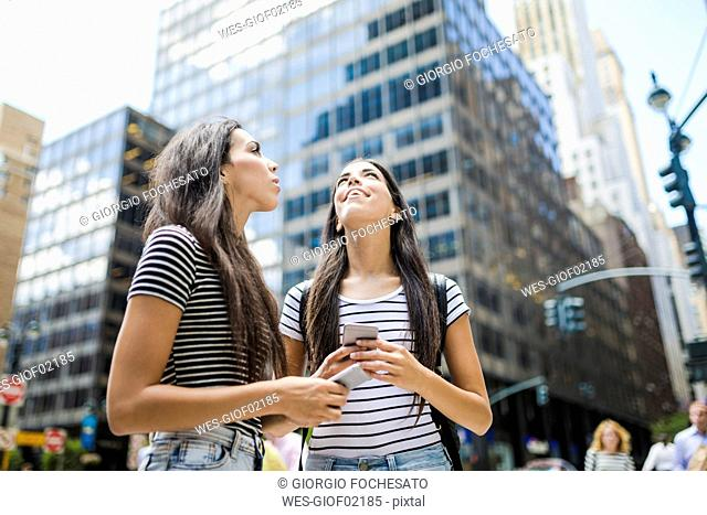 USA, New York City, two twin sisters with cell phones in Manhattan looking up
