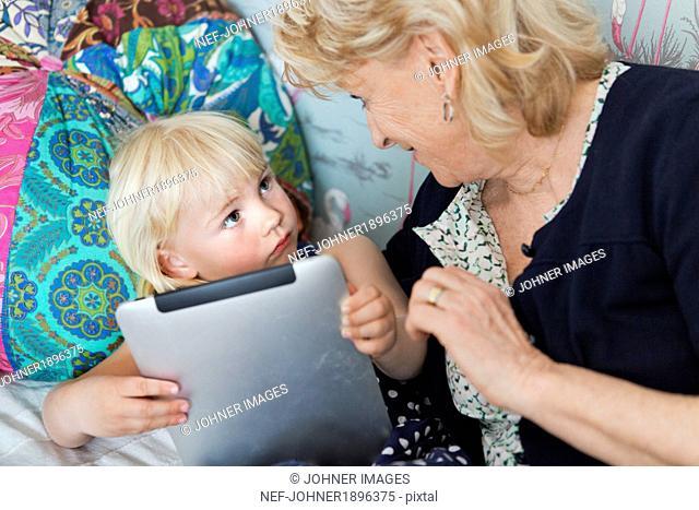 Grandmother with gramdchild using digital tablet