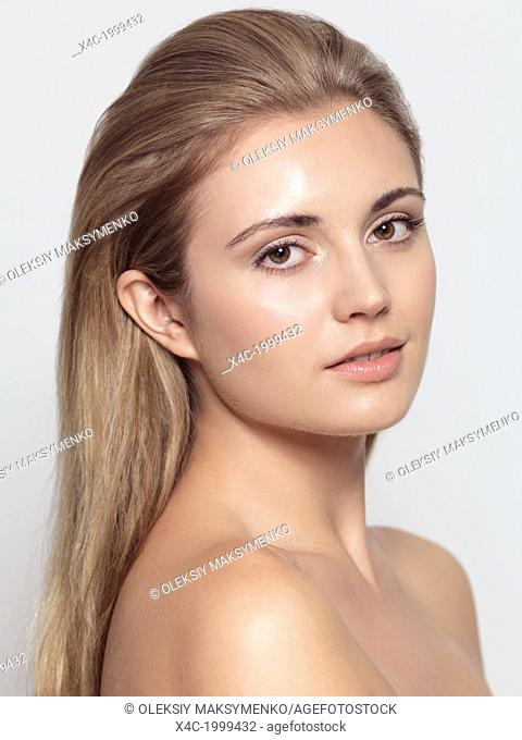 Beauty portrait of young woman with natural clean makeup and long light brown hair isolated on light gray background