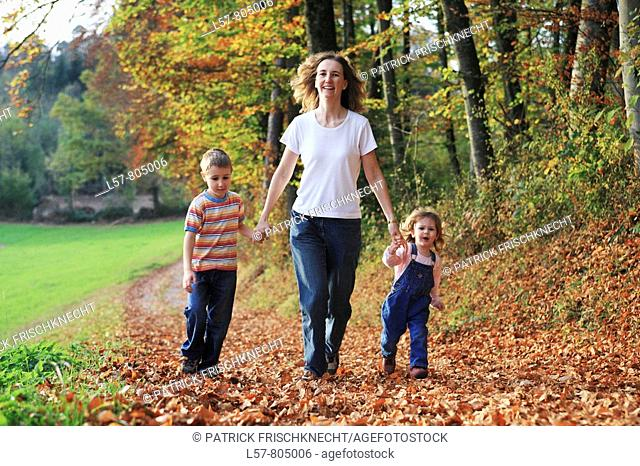 Mother with daughter and son running hand in hand on path full of leaves in fall, having fun and laughing, autumn foliage covering path in forest, autumn, fall