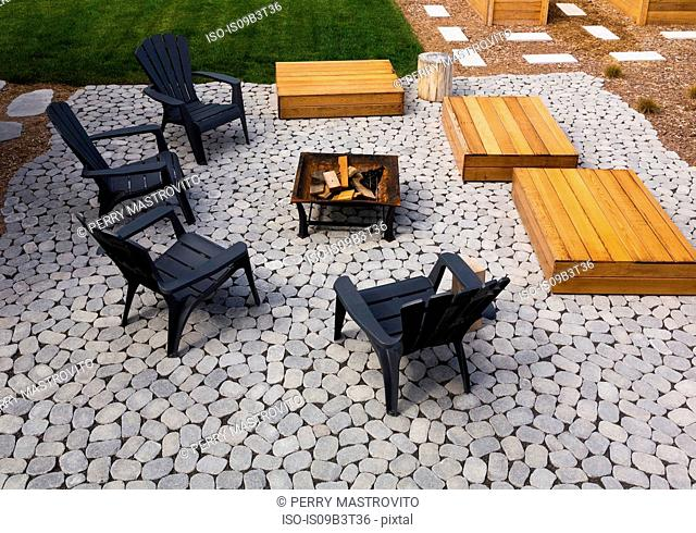 Grey paving stone patio with black Adirondack sitting chairs, slightly raised flat rectangular red cedar wooden bench platforms around a metal firepit in...