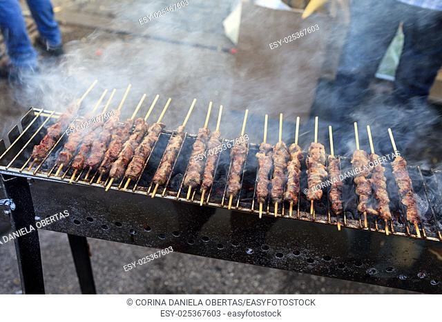 Street vendor preparing grilled lamb skewers for sale