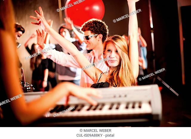 Young woman playing keyboard with people dancing