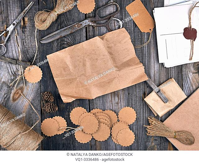 coil of brown rope, paper tags and old scissors on a gray wooden background, objects for making handicrafts