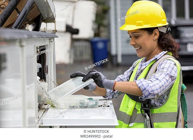 Hispanic female utility worker with box of cable amplifiers at site