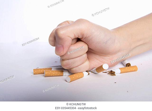 No smoking concept, closeup of clenched fist pounding cigarettes, no smoking