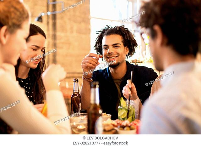 leisure, food, drinks, people and holidays concept - happy friends eating and drinking at bar or cafe