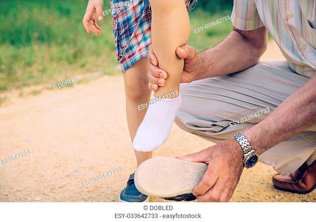 Closeup of grandfather cleaning small stones into the shoe of his grandson over a nature pathway background