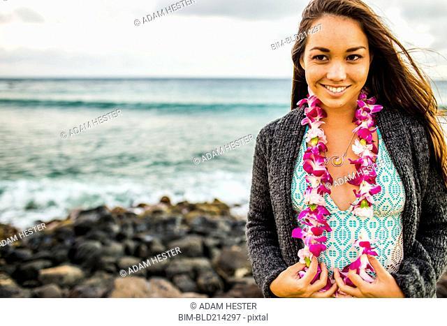 Pacific Islander woman wearing flower lei near rocky beach