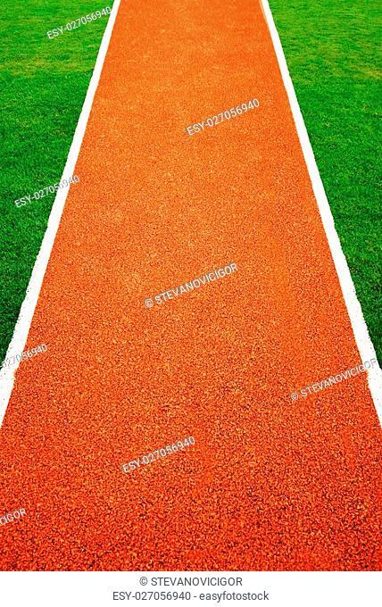 Orange athletics all weather running track texture in green grass