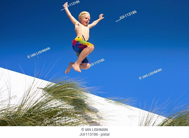 Exuberant boy jumping for joy over sand dune beach hill