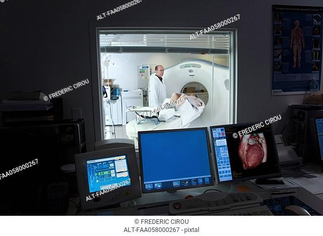 Male doctor standing next to female patient having CAT scan