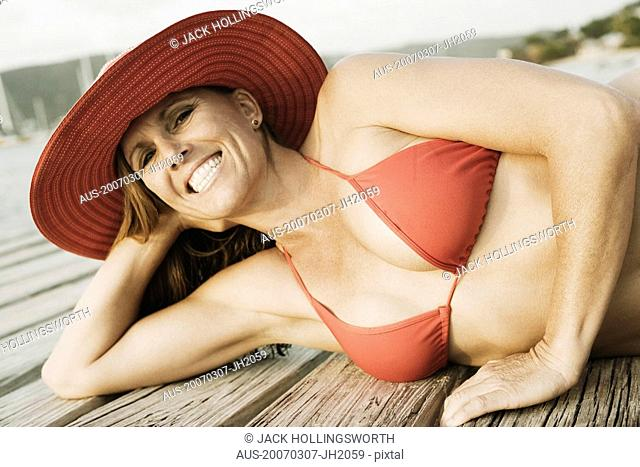 Mid adult woman lying on a pier and smiling
