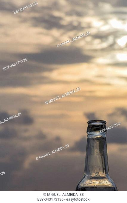 top of a beer glass bottle on blur sunset background