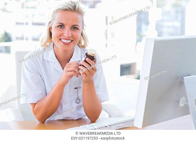 Smiling nurse sitting behind a desk and holding a medicine jar