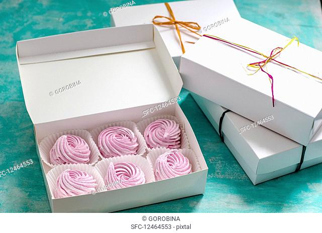 Pink zefir in a gift box on a blue surface
