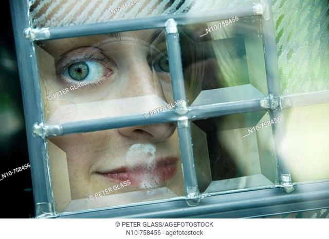 Close-up of a young woman looking out a window
