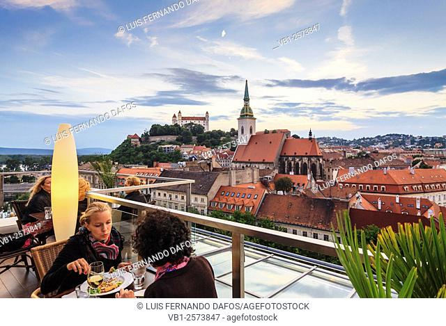 Women at panoramic terrace of Sky restaurant overlooking old town, cathedral and castle in Bratislava, Slovakia
