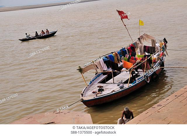 The man take pilgrims and tourists for Holly Ganges River boat trip and boat is the house to live