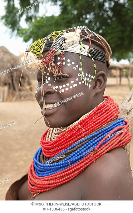 Young Karo woman with lots of colorful necklaces, facial paintings and head adornment, Omo river valley, Southern Ethiopia
