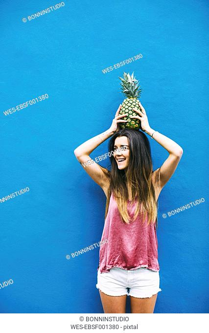 Smiling young woman holding pineapple at blue wall