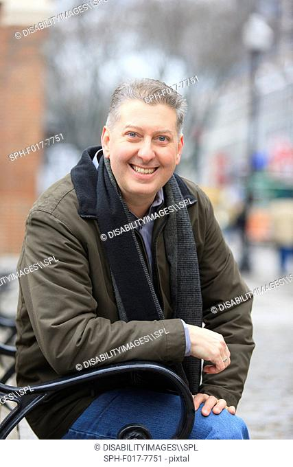 Portrait of a man sitting on a bench and smiling, Boston, Suffolk County, Massachusetts, USA