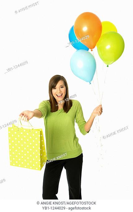 Teenage girl holding balloons and shopping bag or gift bag