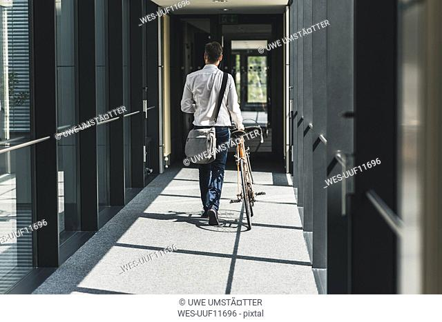 Businessman pushing bicycle in office passageway