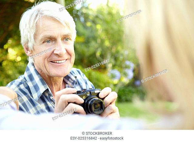 Senior couple taking photo outdoors