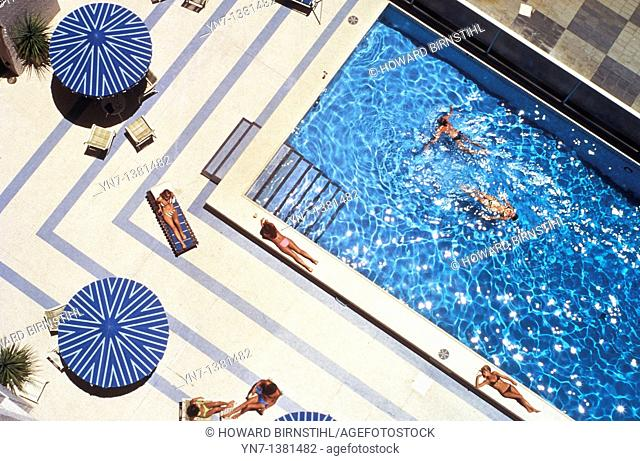 seen from above a few sunbathers and swimmers take advantage of of their luxury pool