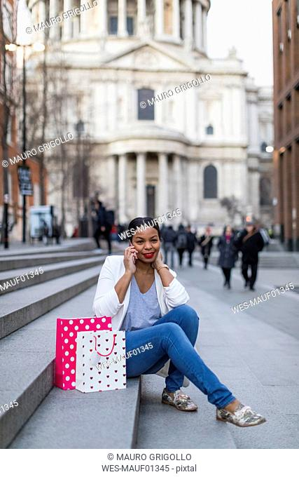 UK, London, woman with shopping bags on cell phone sitting on stairs in the city