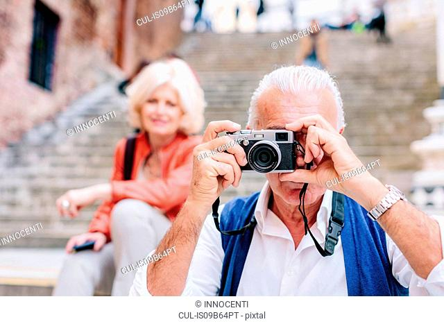 Senior male tourist taking photographs in Siena, Tuscany, Italy