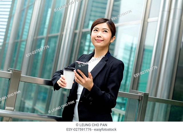 Businesswoman holding coffee cup and cellphone