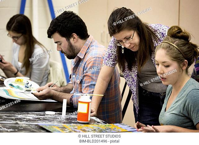 Teacher helping student in art class