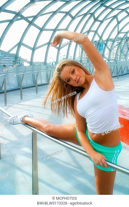 sexy blond woman in sportswear, stretching