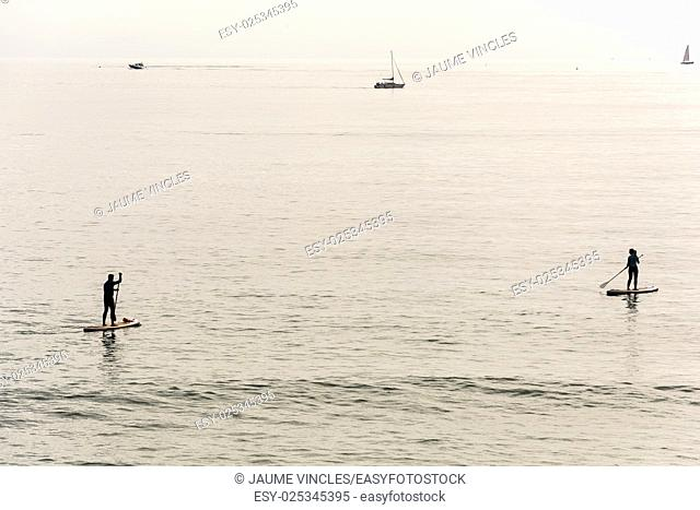 Couple practicing surf paddle on the Barcelona Coast