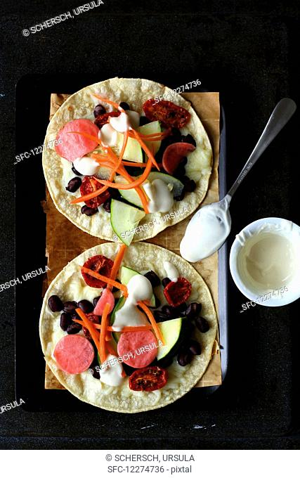 Tacos with cheese, beans, cucumbers, tomatoes, carrots and radishes