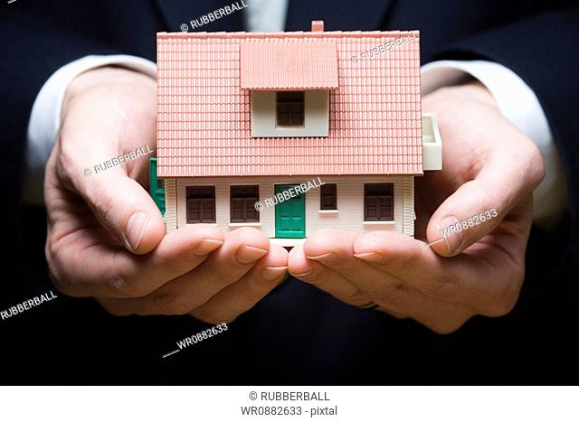 Mid section view of a businessman holding a model house in his hands