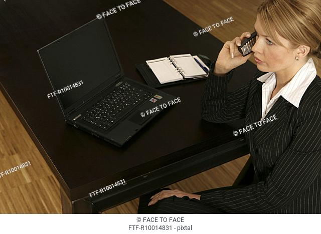 Blonde businesswoman works on a laptop as she converses on the cell phone