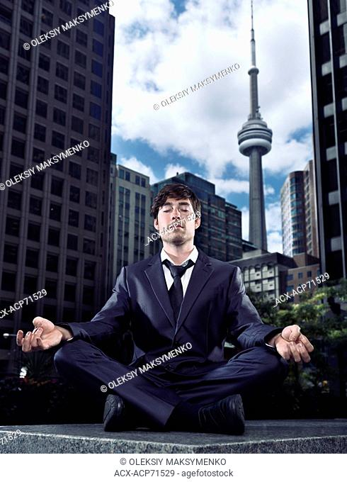 Conceptual portrait of a businessman sitting crosslegged meditating outdoors in downtown Toronto with CN tower and office buildings in the background